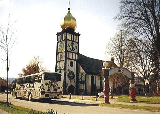 Der Hundertwasser-Bus vor der von Hundertwasser gestalteten St. Barbara Kirche (Österreich)